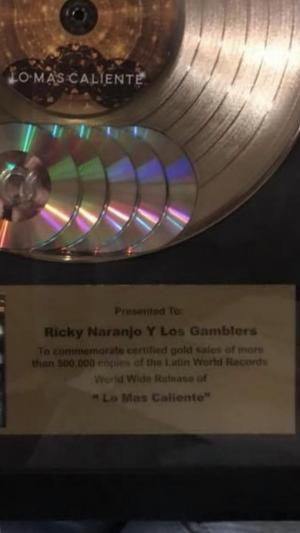 "presented to Ricky Naranjo y Los Gamblers to commemorate gold sales of more than 500,000 copies of the Latin World Records World Wide Release of ""Lo Mas Caliente"""